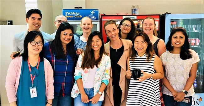 Elaine standing with ten coworkers