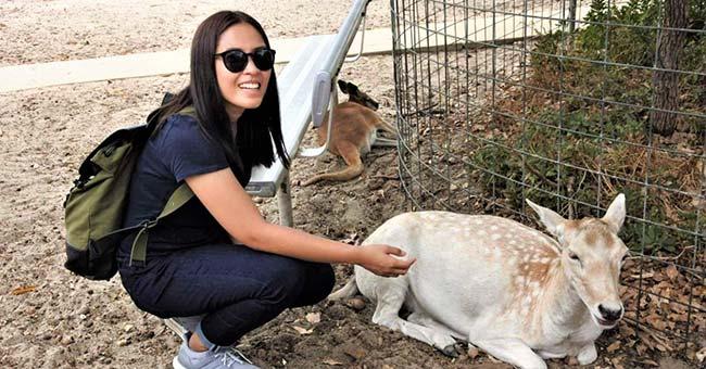Sheela petting a deer at a zoo