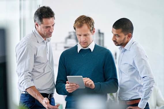 Three men gathered around a tablet device